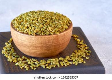 Uncooked cracked freekeh grain in wooden bowl