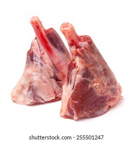 Uncooked goat meat leg shank roasting joints isolated on a white studio background
