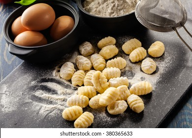 Uncooked homemade gnocchi on black cutting board