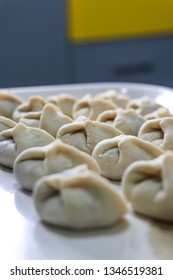 Uncooked homemade Russian pelmeni being prepared in the kitchen. pelmeni stuffed with meat
