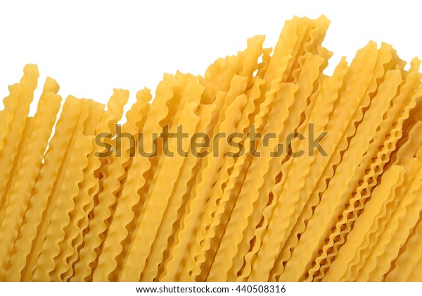 Uncooked Italian pasta mafaldine on a white background