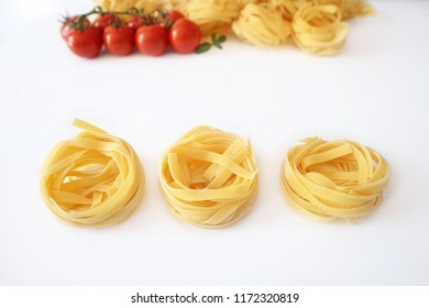 Uncooked Italian pasta on a white background. Raw tagliatelle, isolated. Dry fettuccine, pappardelle made from wholewheat flour. Space for text.