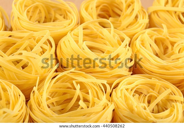 Uncooked Italian pasta tagliatelle nests close up as background