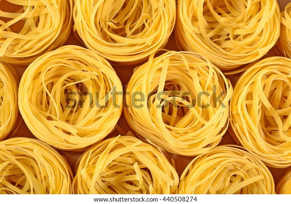 Uncooked Italian pasta tagliatelle nests as background texture