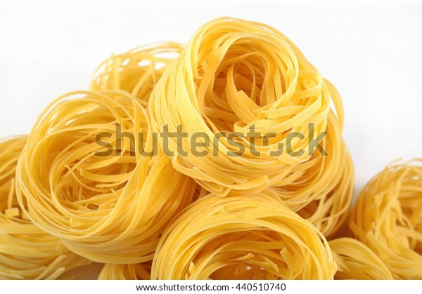Uncooked Italian pasta tagliatelle nests on a white background