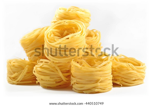 Uncooked Italian pasta tagliatelle nests on a white background