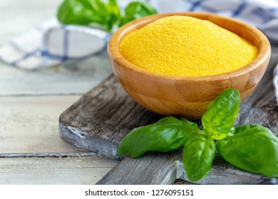 Uncooked Italian typical polenta in a wooden bowl and green basil on an old serving board, selective focus.