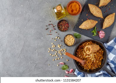uncooked kibbeh of ground beef meat mixed with bulgur, fried minced meat with pine nuts, spices , garlic and herbs. ingredients in bowls on a concrete table, view from above, flat lay, copy space