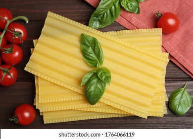 Uncooked lasagna sheets with cherry tomatoes and basil on wooden table, flat lay