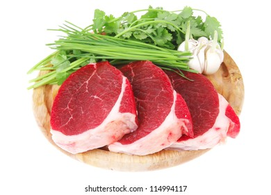 uncooked meat : raw fresh beef pork fillet ready to cooking with garlic and green stuff over wood isolated over white background