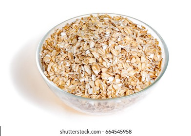Uncooked oat flakes in glass bowl on white background. Healthy food. Close up, top view
