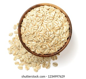 uncooked oatmeal in the wooden bowl, isolated on the white background, top view