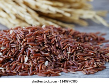 Uncooked organic red rice on wooden table background.