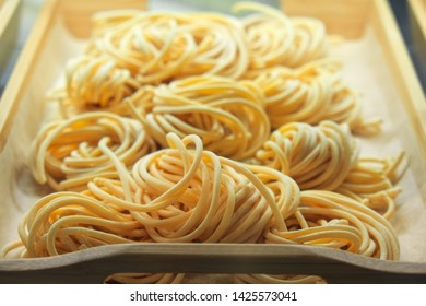 Uncooked pasta closeup in on wooden tray in the shop window. Italian foods concept of spaghetti and menu design
