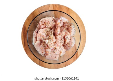 Uncooked poultry meat with spices. Sliced pieces of raw chicken fillet sprinkled with various dry seasonings in a blue glass bowl on a round wooden cutting board. Isolated on white background