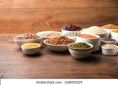 Uncooked pulses,grains and seeds in White bowls over wooden background. selective focus