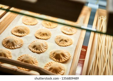 Uncooked Ravioli mix on wooden tray in the shop window. Different kind of dry homemade dumpling. Italian foods concept and menu design.