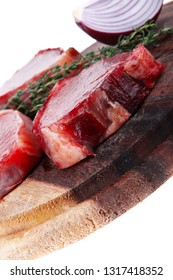 uncooked raw beef fillet with thyme twig on wooden plate isolated over white background