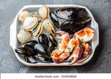 Uncooked raw fresh seafood - mussels, clams, vongole and crabs on ice on blac stone slate background.