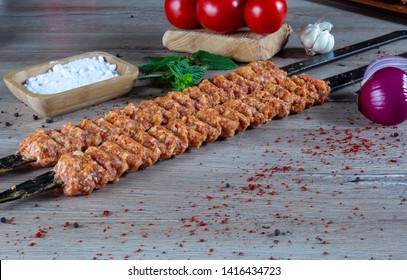 uncooked (raw) meat and Turnspit skewing kebap or kebab on metal skewer in the kebab restaurant. Skewering Kebab. Traditional Kebab