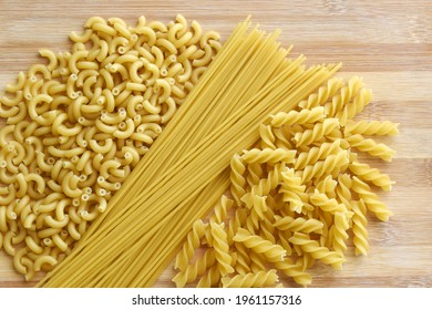 Uncooked raw spaghetti, elbow and fusilli pasta on a chopping board.