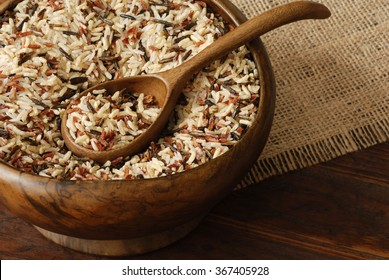Uncooked rice blend (wild, brown, red, and white ) in vintage, handcrafted bowl on rustic wood background.  Closeup with shallow dof.