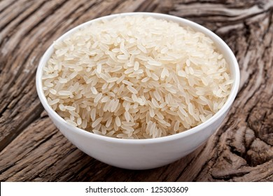 Uncooked rice in a bowl on a dark wooden table.