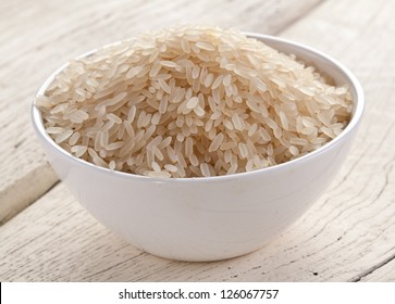 Uncooked rice in a bowl on a white wooden table.