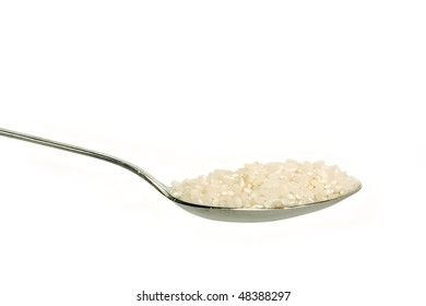 Uncooked rice on a spoon, isolated on white background