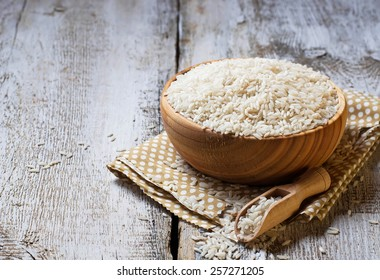 Uncooked rice in a wooden bowl. Selective focus. Space for text