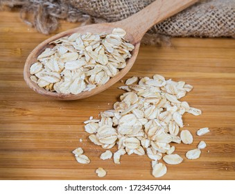 Uncooked rolled oats in the wooden spoon and scattered beside on the bamboo wooden cutting board, close-up in selective focus