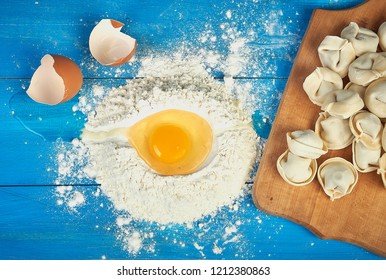 Uncooked russian pelmeni on cutting board and ingredients for homemade pelmeni with fresh egg on blue table