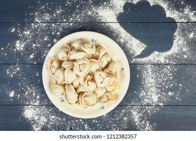 Uncooked russian pelmeni on cutting board, homemade pelmeni on blue table with dialog cloud