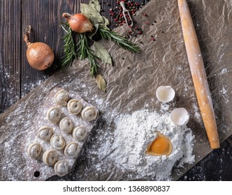 Uncooked russian pelmeni on cutting board and ingredients for homemade pelmeni on white table. Process of making pelmeni, ravioli or dumplings with meat. Top view.