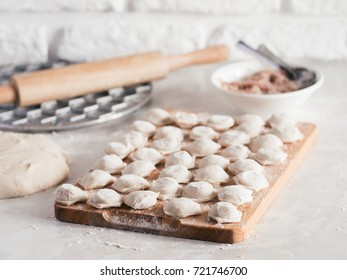 Uncooked russian pelmeni on cutting board and ingredients for homemade pelmeni on white table. Process of making pelmeni, ravioli or dumplings with meat. Copy space