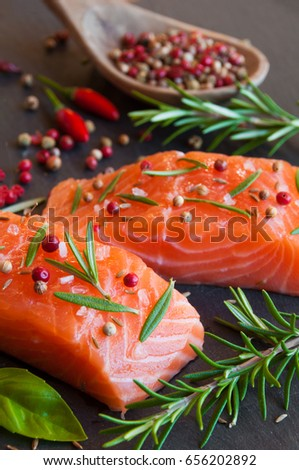Uncooked salmon fillets with rosemary and pepper
