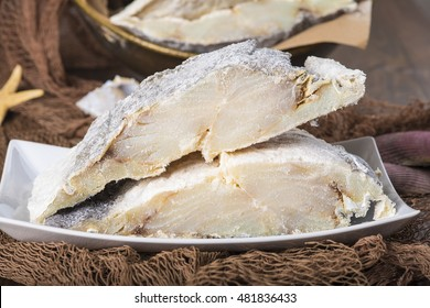 Uncooked salted preserved cod cut in portions on fishing nets