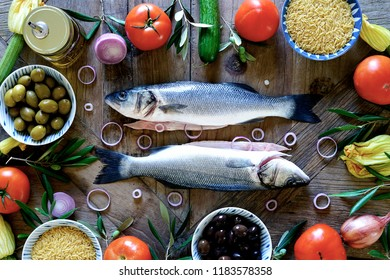 Uncooked seabass with ingredients on wooden table. Food flat lay