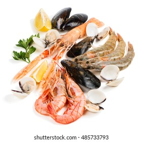Uncooked seafood (langoustine,  shrimp,  shellfish,  mussel,  clam) decorated with lemon and parsley isolated on white background.