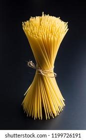 Uncooked spaghetti pasta on black background.