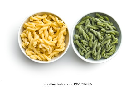Uncooked spinach gemelli pasta in bowl isolated on white background.