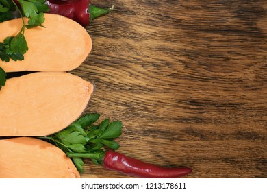 Uncooked sweet potato slices with pepers chilli and greenery on a dark wooden board background. Horizontal.