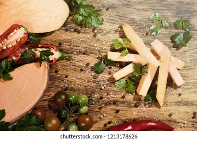 Uncooked sweet potato slices with pepers chilli, tomatoes and greenery on a dark wooden board background. Horizontal.