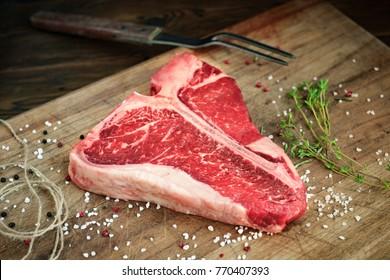 uncooked t bone steak of beef on the butcher's Board