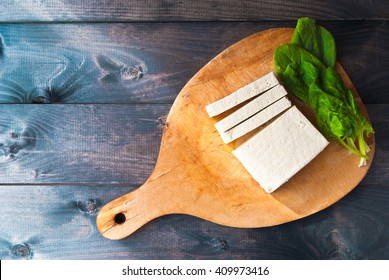 Uncooked tofu slices and green leaves of fresh spinach on cutting board and rustic wooden background