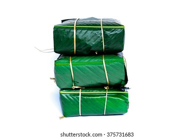Uncooked Vietnamese Chung Cake isolated on white. Its a square glutinous sticky rice cake, stuffed with pork meat, green beans and wrapped in bamboo leaf.  Traditional Vietnamese New Year. Copy space.
