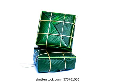 Uncooked Vietnamese Chung Cake isolated on white. Itâ??s a square glutinous sticky rice cake, stuffed with pork meat, green beans and wrapped in bamboo leaf.  Traditional Vietnamese New Year (Tet) food.