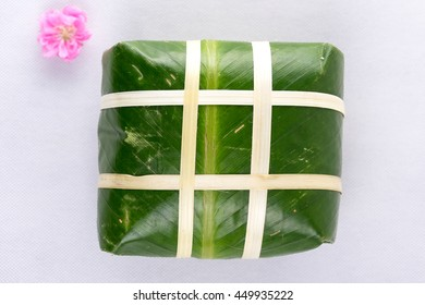 Uncooked Vietnamese Chung Cake isolated on white. It's a square glutinous sticky rice cake, stuffed with pork meat, green beans and wrapped in bamboo leaf. Traditional Vietnamese New Year (Tet) food.