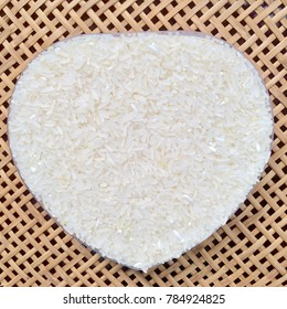 Uncooked white rice (Thai Jasmine rice) in heart shape on bamboo tray