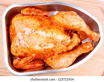 Uncooked whole marinated chicken in aluminum foil tray